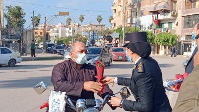 """صورة رجال الشرطة يوزعون الورود والحلوى وكتيبات بـ""""كفر الشيخ"""" .. والمواطنون يلتقطون الصور التذكارية"""